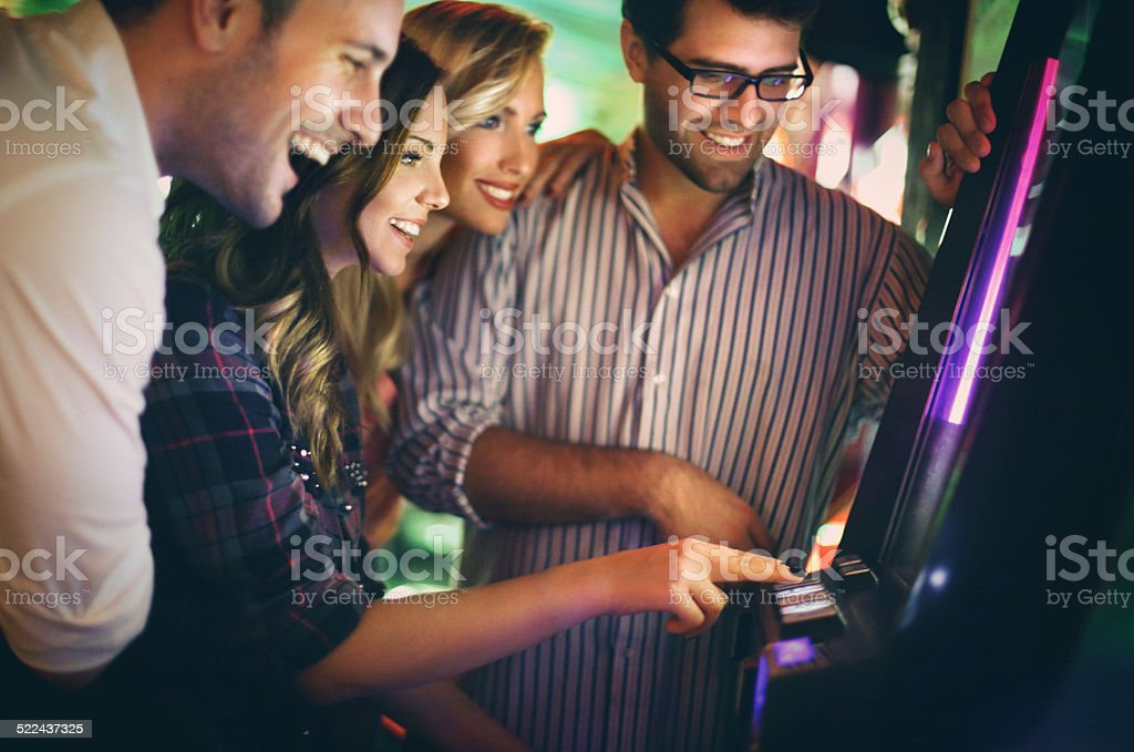 Group of young adults having fun in casino. stock photo