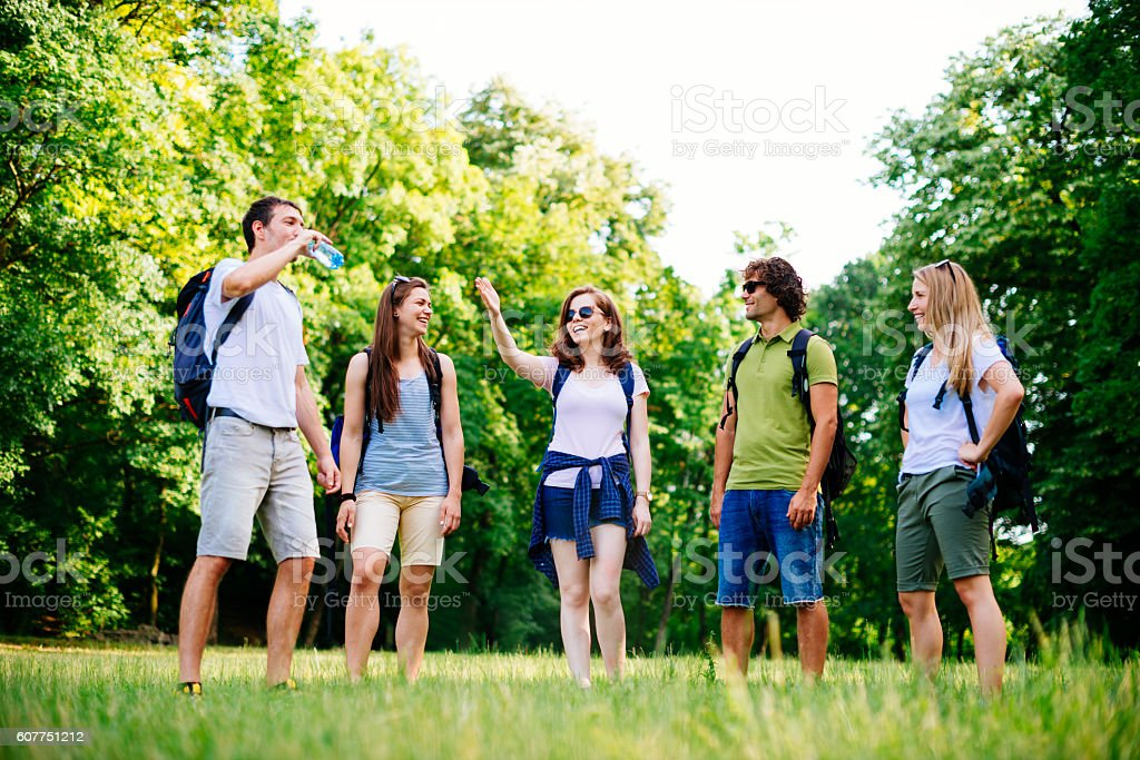 Group of young adults practice orienteering in nature stock photo