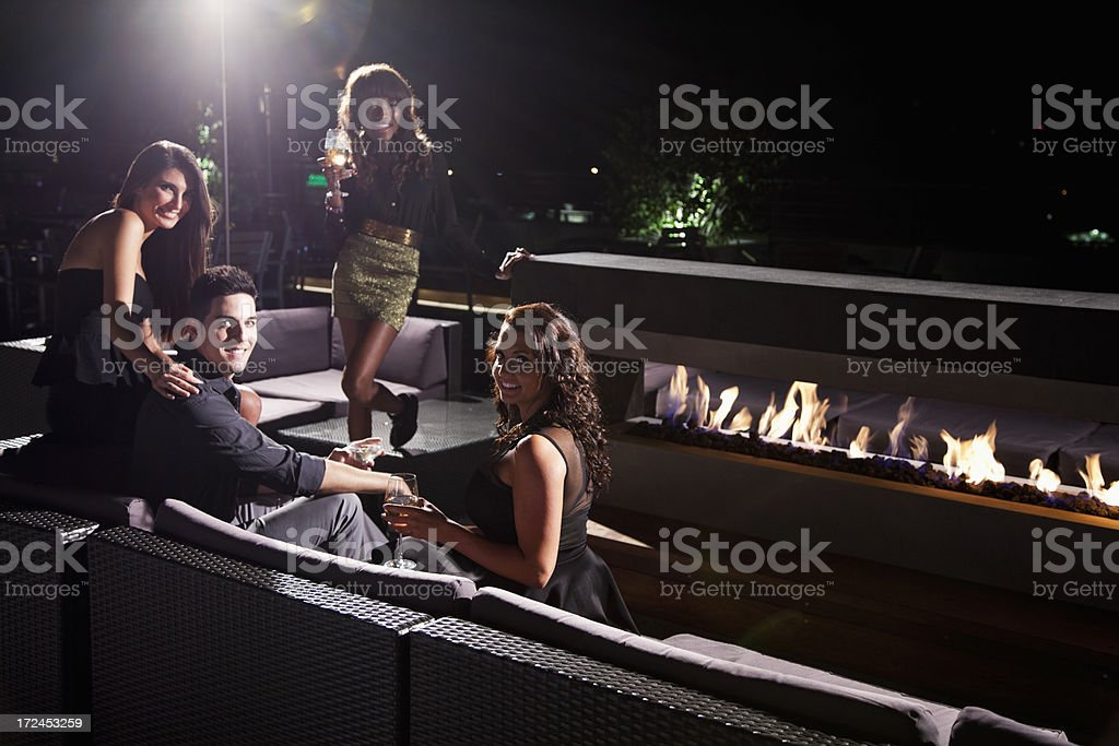 Group of young adults sitting by fireplace stock photo
