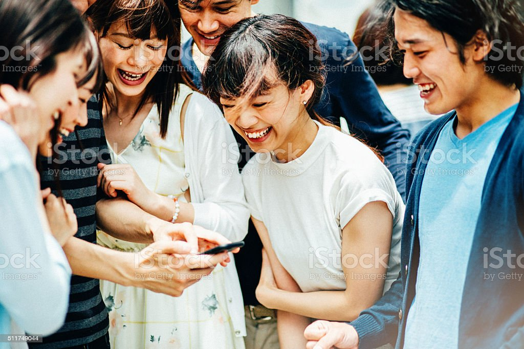 Group of young Asian ethnicity friends with smart phone stock photo