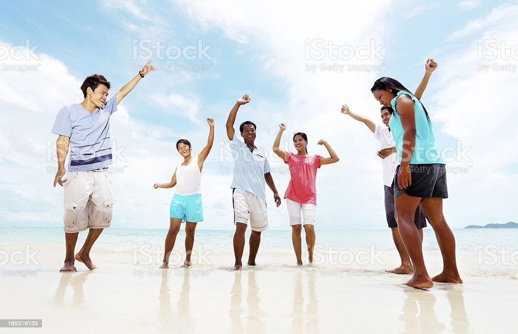 Group of young Asian people enjoying at the beach royalty-free stock photo