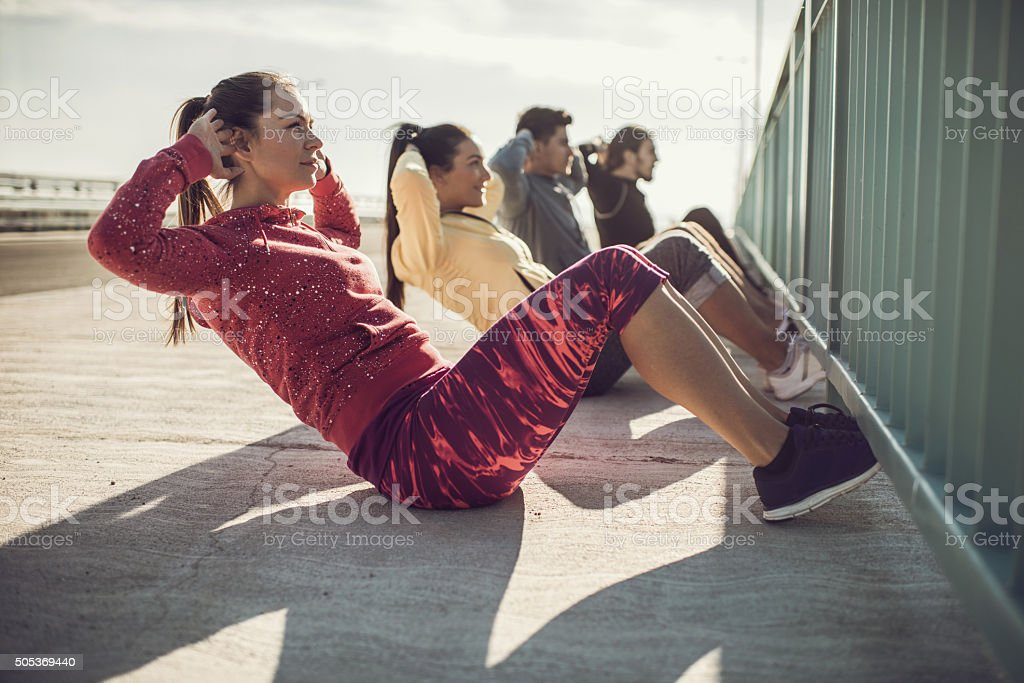 Group of young athletes doing sit ups on a sidewalk. stock photo