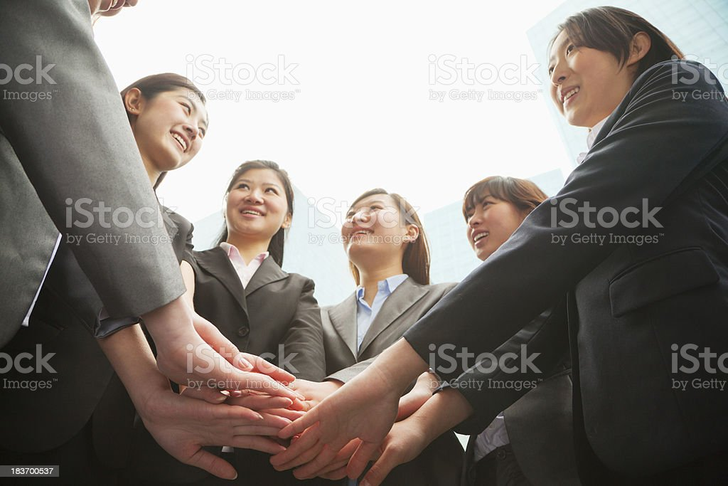 Group of young businesswoman putting hands together in a circle royalty-free stock photo