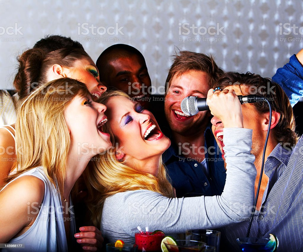 Group of young cheerful people singing stock photo