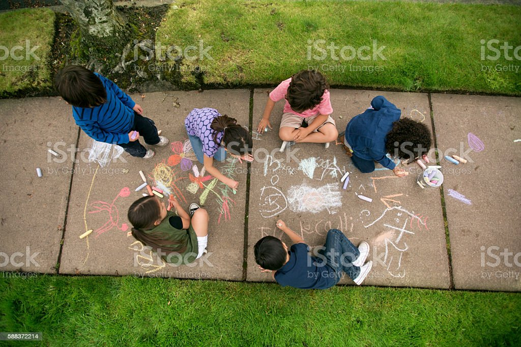 Group of young children drawing with chalk on the sidewalk stock photo