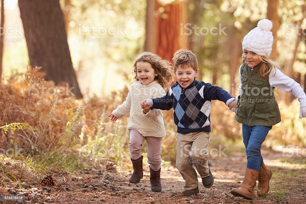 Group Of Young Children Running Along Path In Autumn Forest stock photo