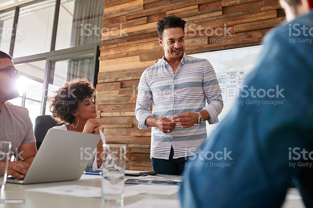 Group of young designers brainstorming in boardroom stock photo