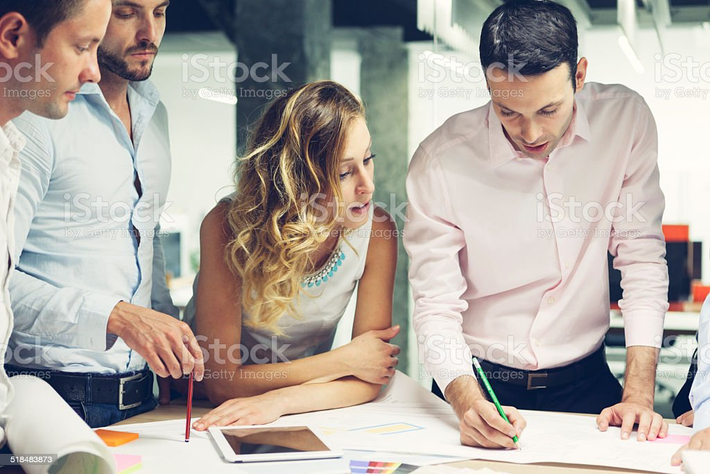 Group of Young Designers reviewing new project in the office. stock photo
