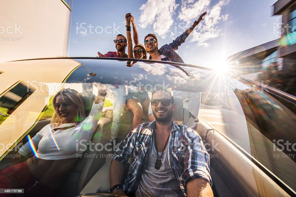 Group of young excited friends having fun on road trip. stock photo