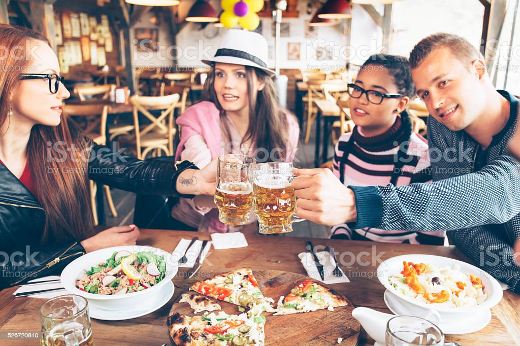 Group of young friends celebrating in restaurant stock photo