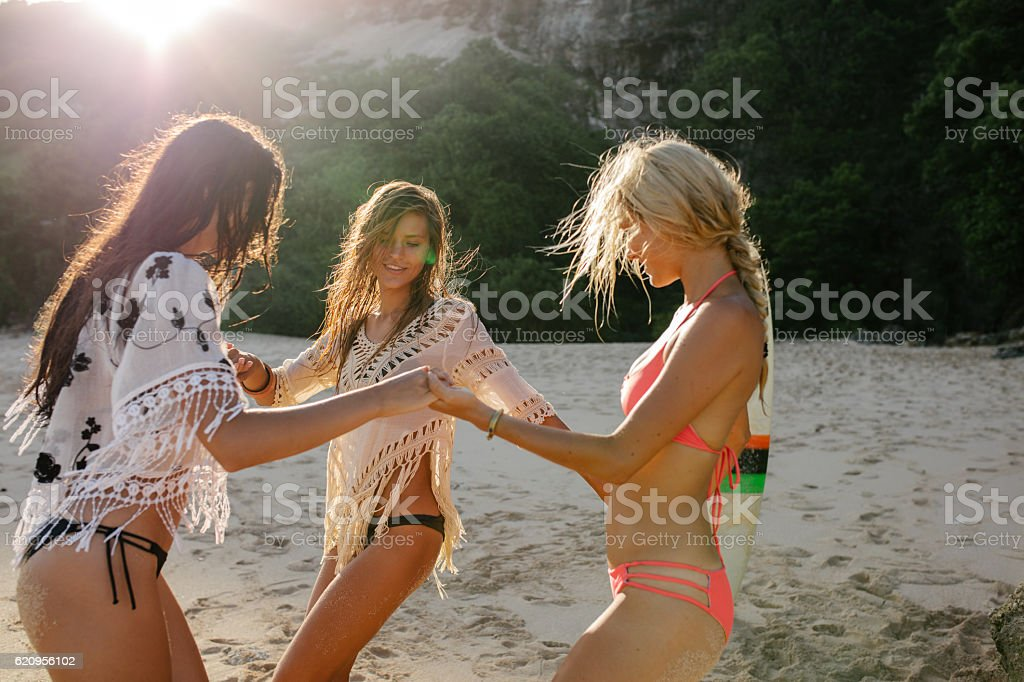 Group of young friends dancing on the beach stock photo