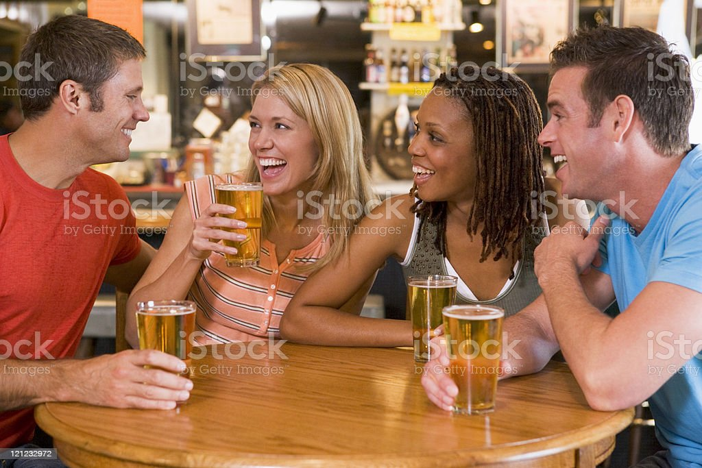 Group of young friends drinking and laughing in a bar royalty-free stock photo