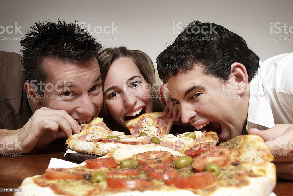 Group of young friends eating pizza off a table royalty-free stock photo