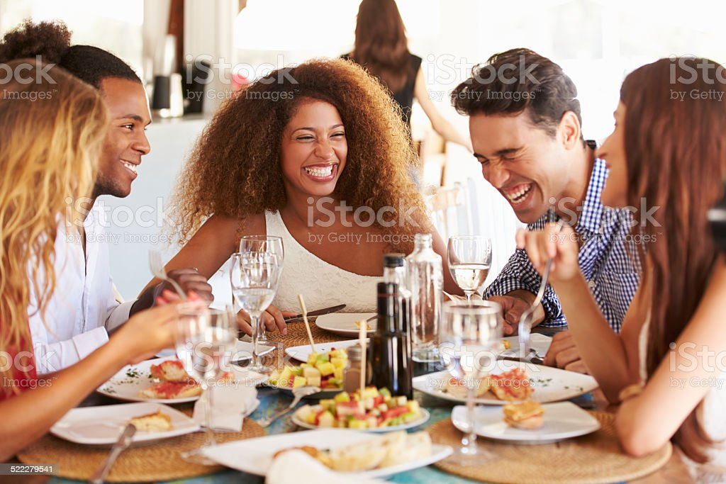 Group Of Young Friends Enjoying Meal In Outdoor Restaurant stock photo