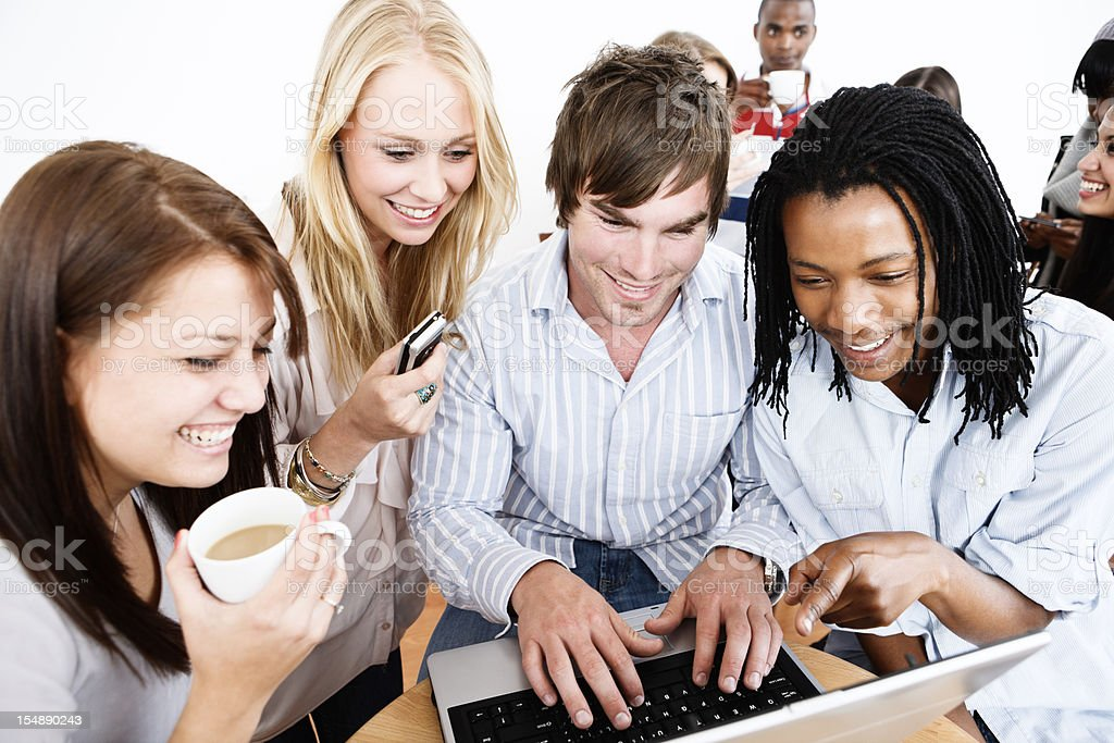 Group of young friends gather round laptop, smiling royalty-free stock photo