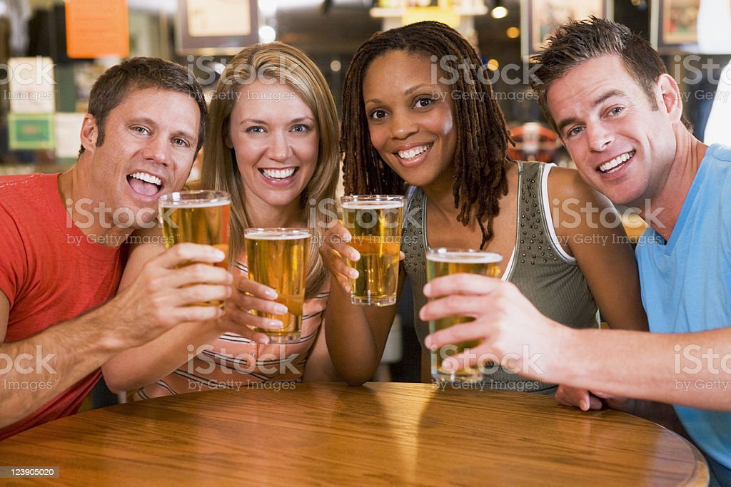Group of young friends in bar toasting to the camera royalty-free stock photo