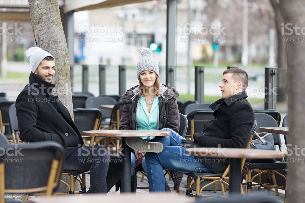 Group of young friends is resting in an outdoor caffe. stock photo