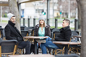 Group of young friends is resting in an outdoor caffe.