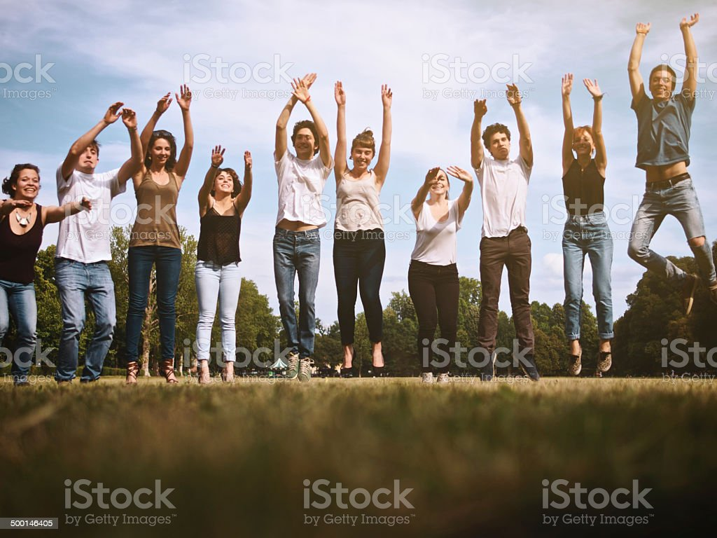 Group of young friends jumping in a park stock photo