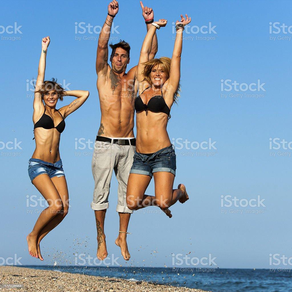 Groupe de jeunes amis, sauter sur la plage. photo libre de droits
