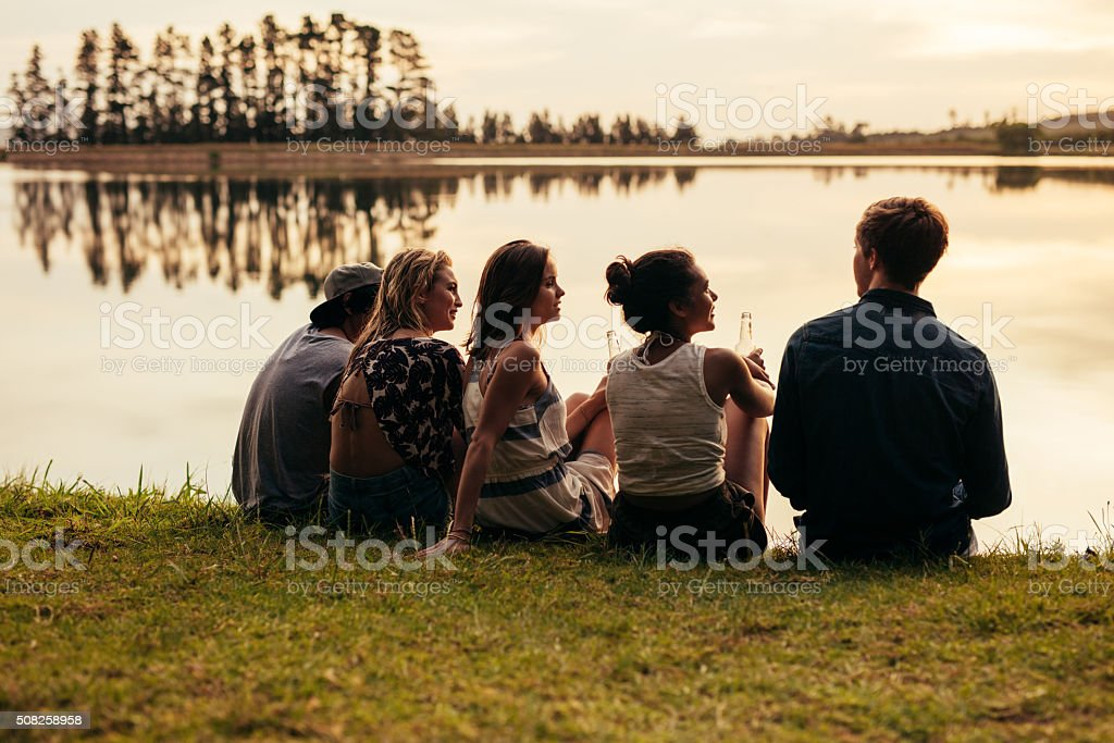 Group of young friends relaxing by a lake stock photo