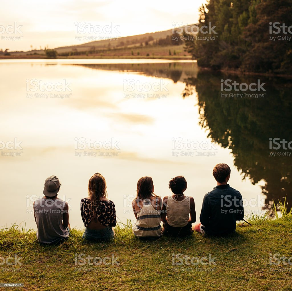 Group of young friends sitting by a lake stock photo