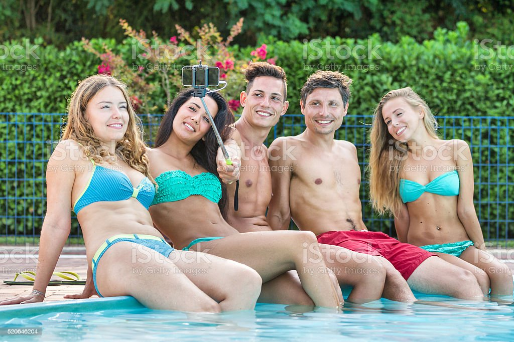 Group of young friends taking selfie at poolside stock photo