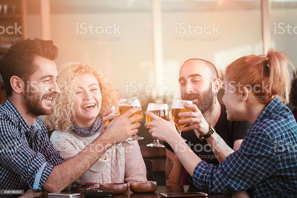 Group of young friends toasting in a bar stock photo