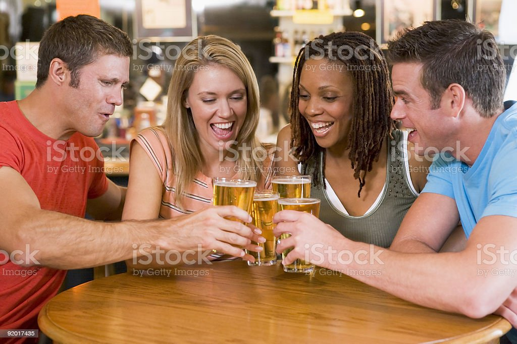 Group of young friends toasting in a bar royalty-free stock photo