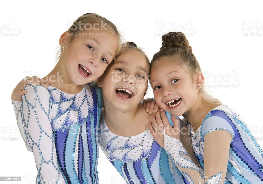 Group of young girl gymnasts in blue and purple uniforms royalty-free stock photo