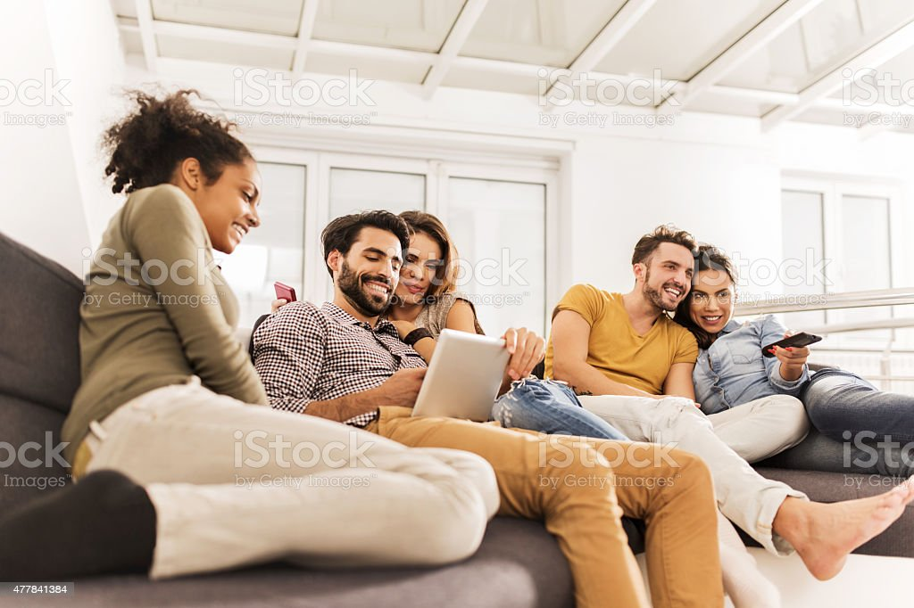 Group of young happy friends relaxing together at home. stock photo
