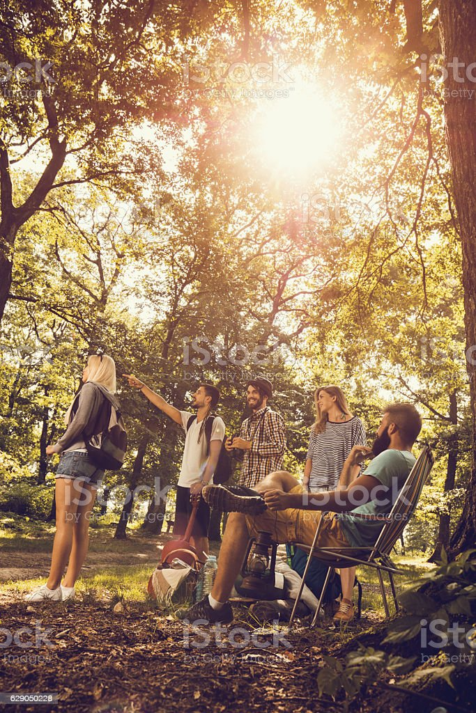 Group of young hikers looking for a place for camping. stock photo