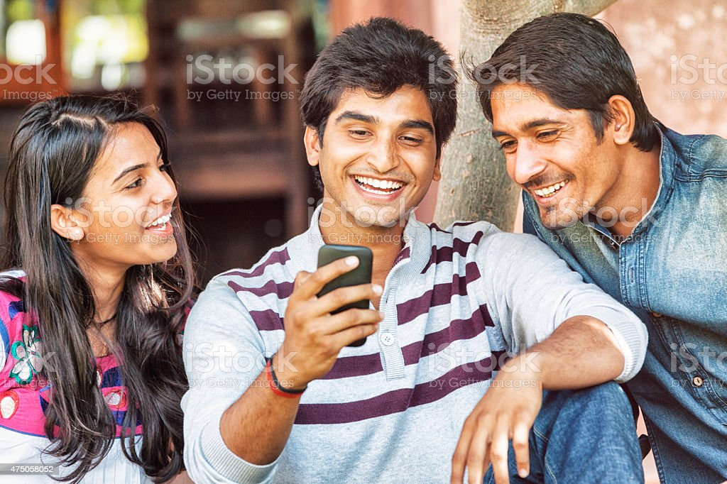 Group of Young Indian Friends Looking at Smart Phone stock photo