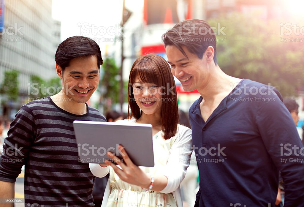 Group of young japanese people with digital tablet, Shibuya, Tokyo. stock photo