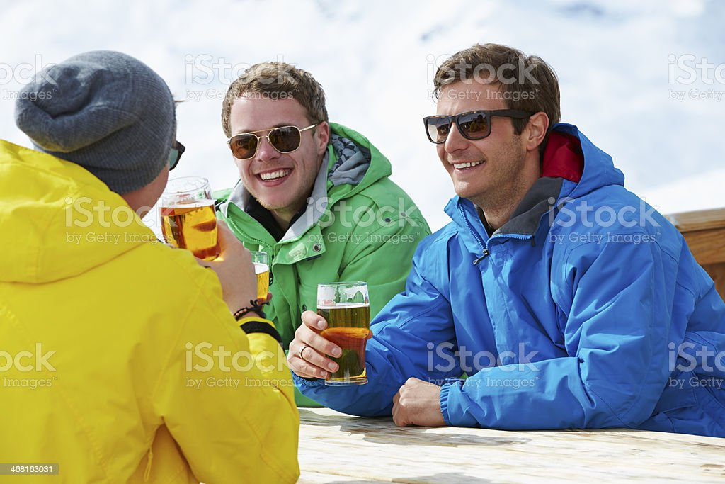 Group Of Young Men Enjoying Drink At Ski Resort stock photo