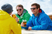 Group Of Young Men Enjoying Drink At Ski Resort