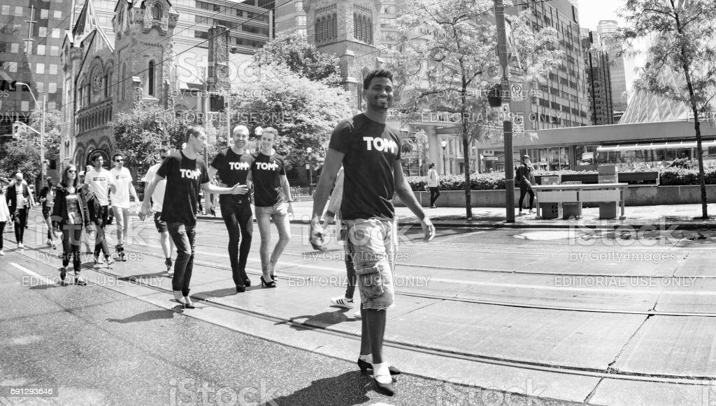 Toronto, Canada - May 31, 2017: Group of young men walking in women shoes stock photo
