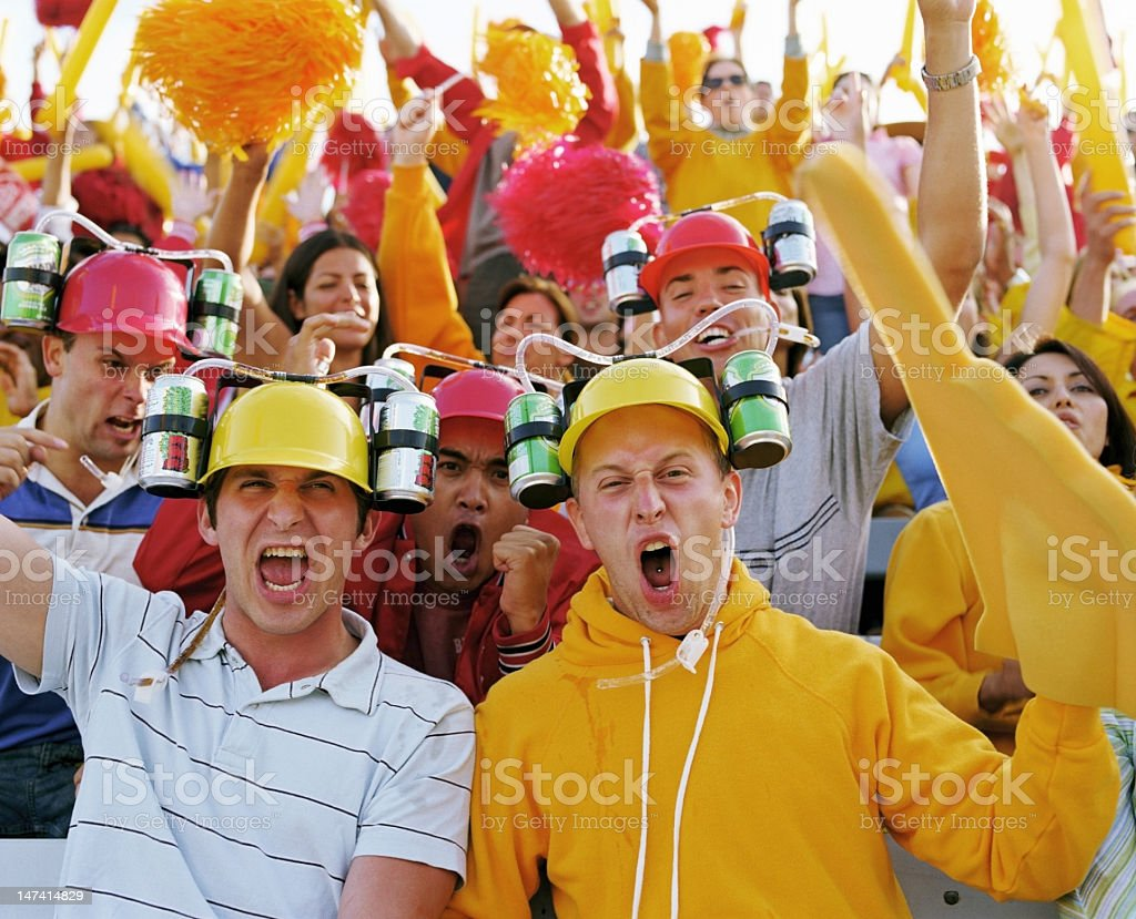 Group of young men wearing drinking helmets, cheering in crowd stock photo