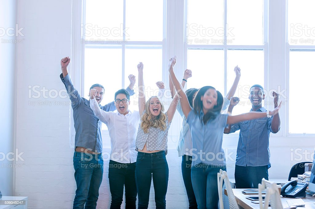 Group of young multi cultural business people celebrating. stock photo