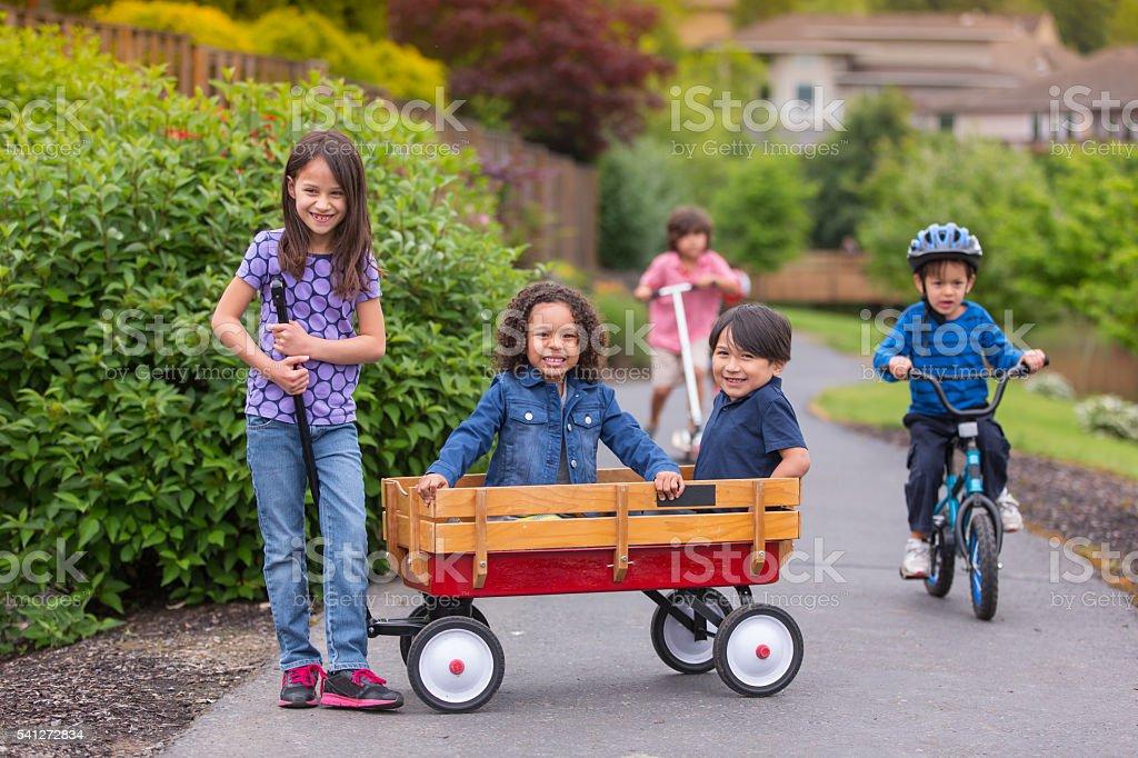 Group of young neighborhood kids smiling and playing stock photo