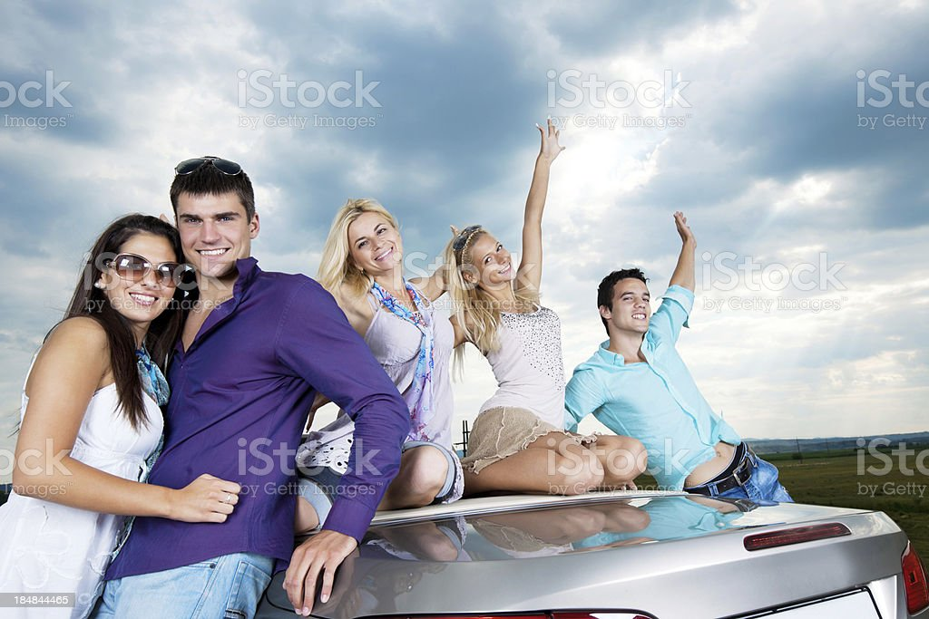 Group of young cheerful people with raised hands is enjoying in the...