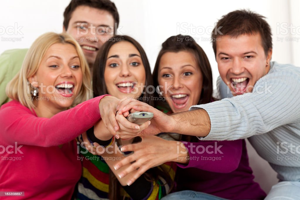 Group of young people are grabbing for remote control royalty-free stock photo