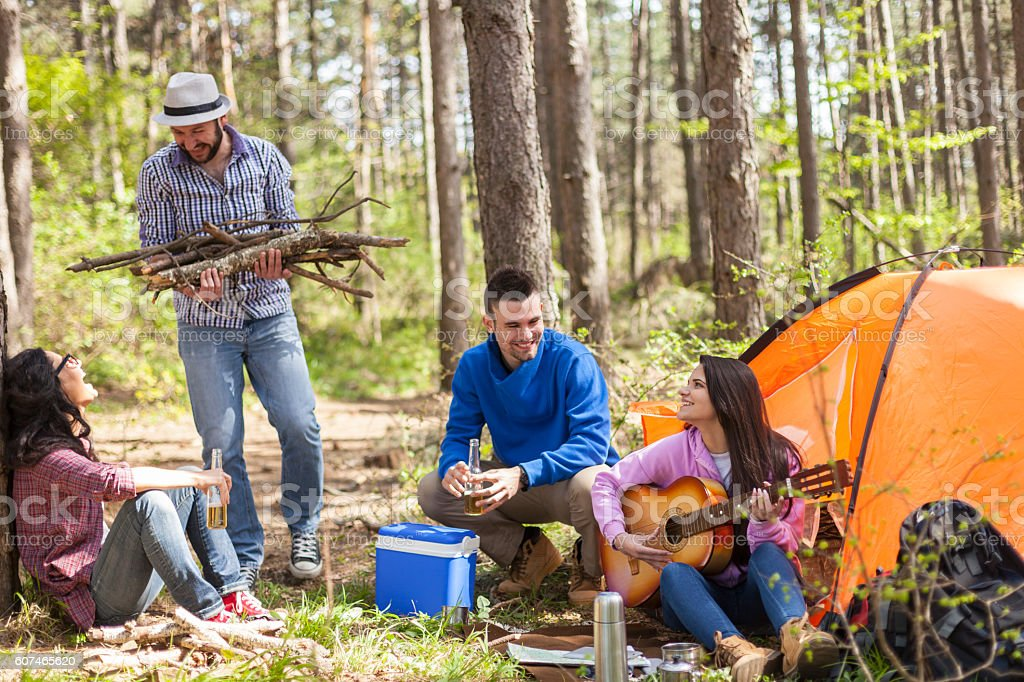 Group of young people camping and playing guitar in forest stock photo