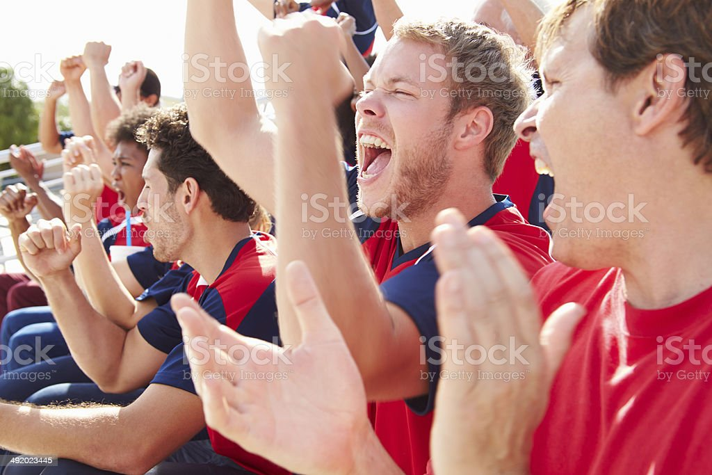 Group of young people cheering at sporting event stock photo