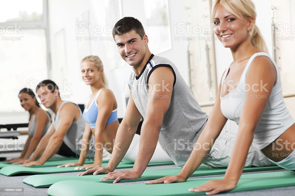 Group of young people doing Pilates exercises royalty-free stock photo