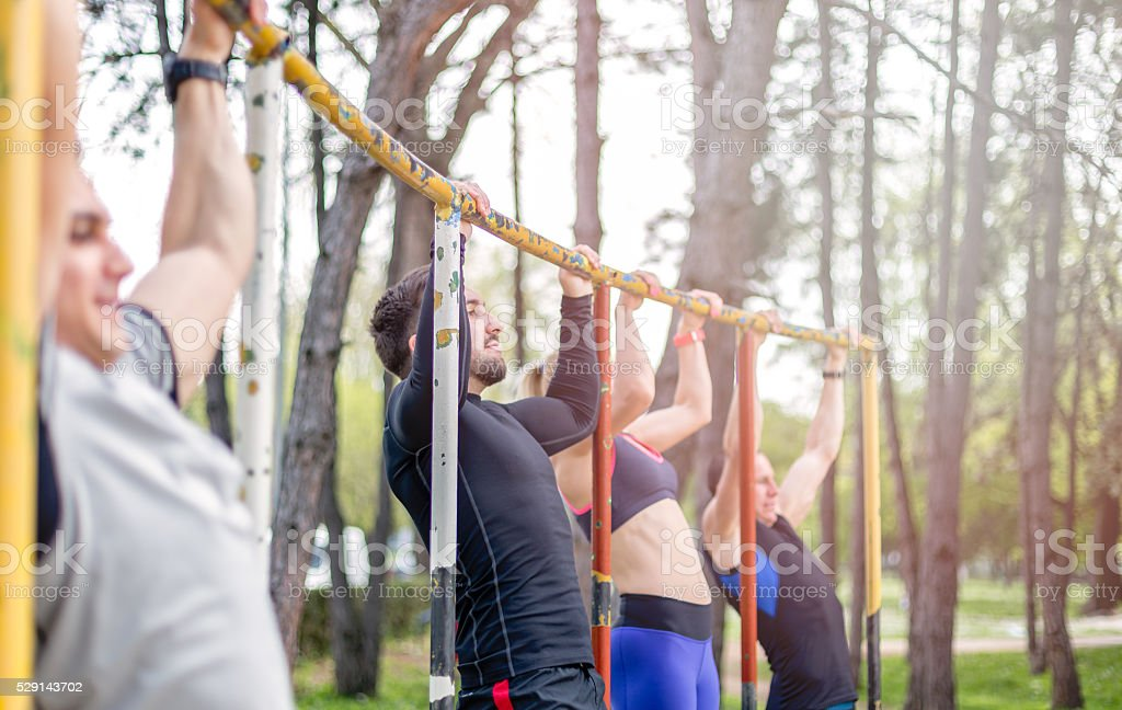 group of young people doing pull ups outdoors stock photo