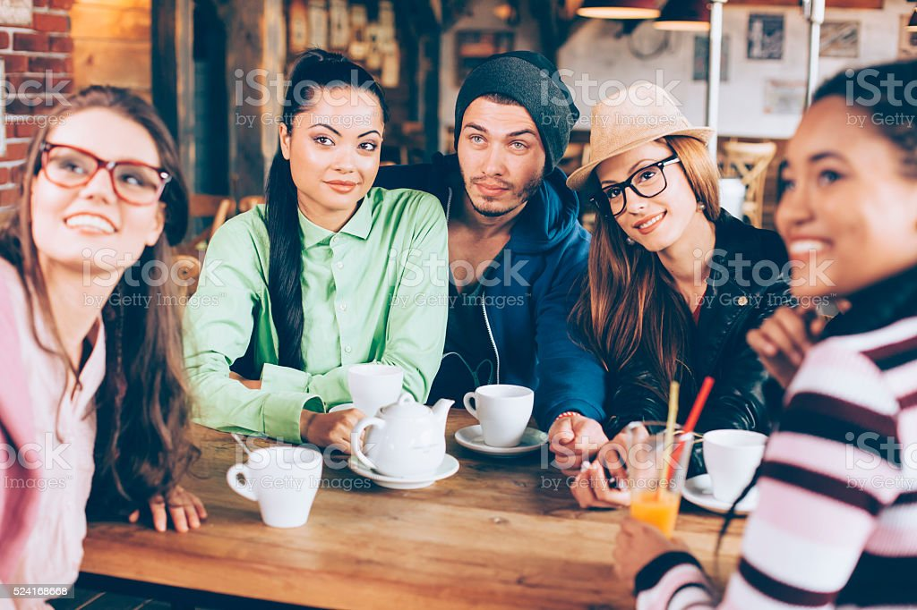 Group of young people drinking coffee together stock photo