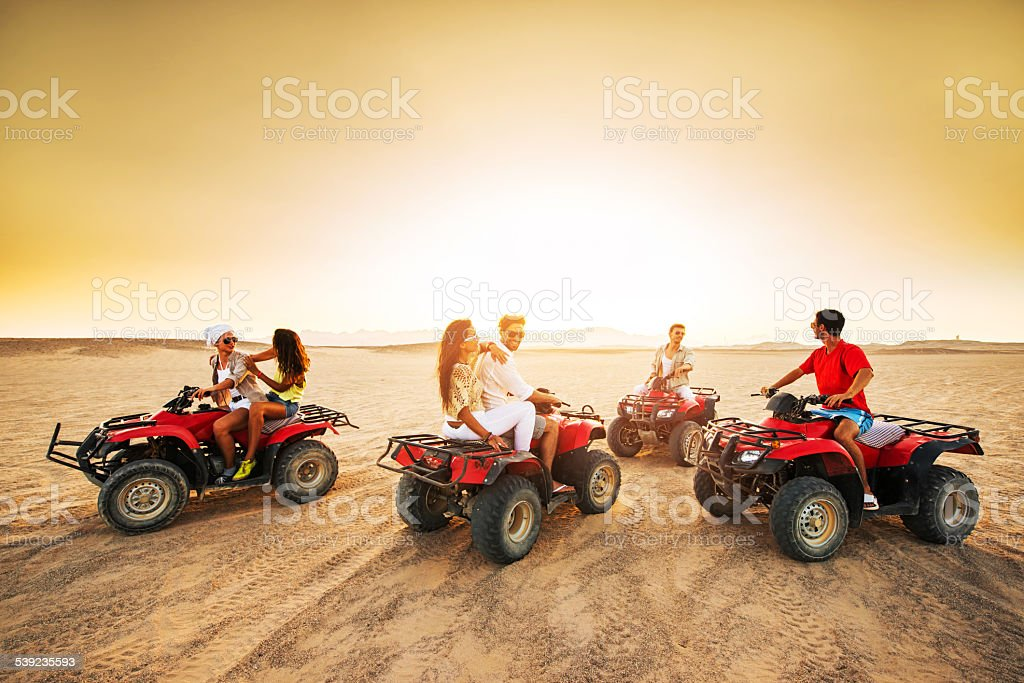 Group of young people driving quad bikes at sunset. stock photo