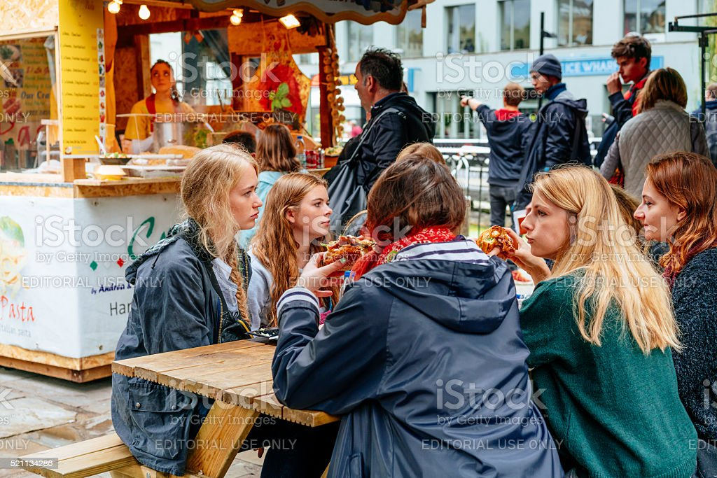 Group of young people eating in Camden Market, London stock photo