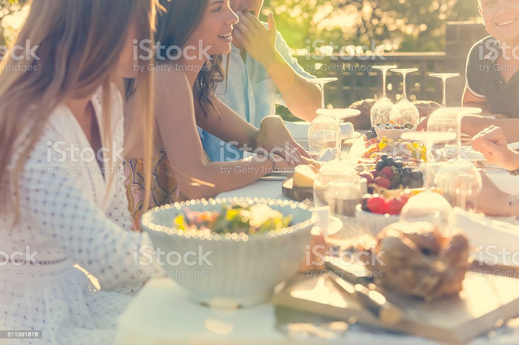 Group of young people eating outdoors. They are all happy, having...